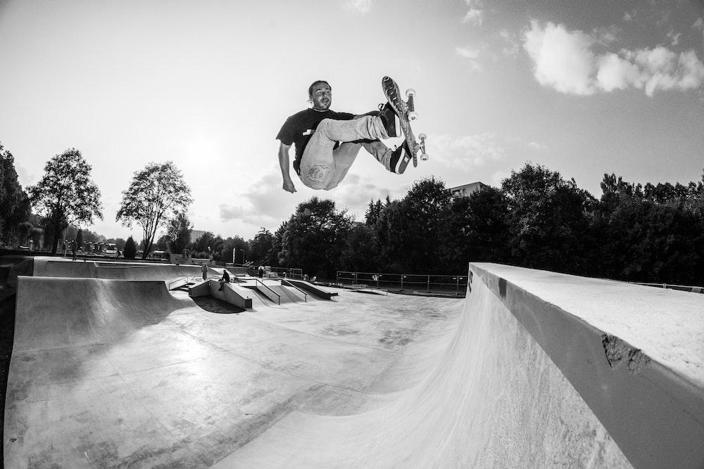 man doing skateboard stunt in skate park