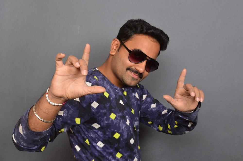 man wearing sunglasses while raising both hands