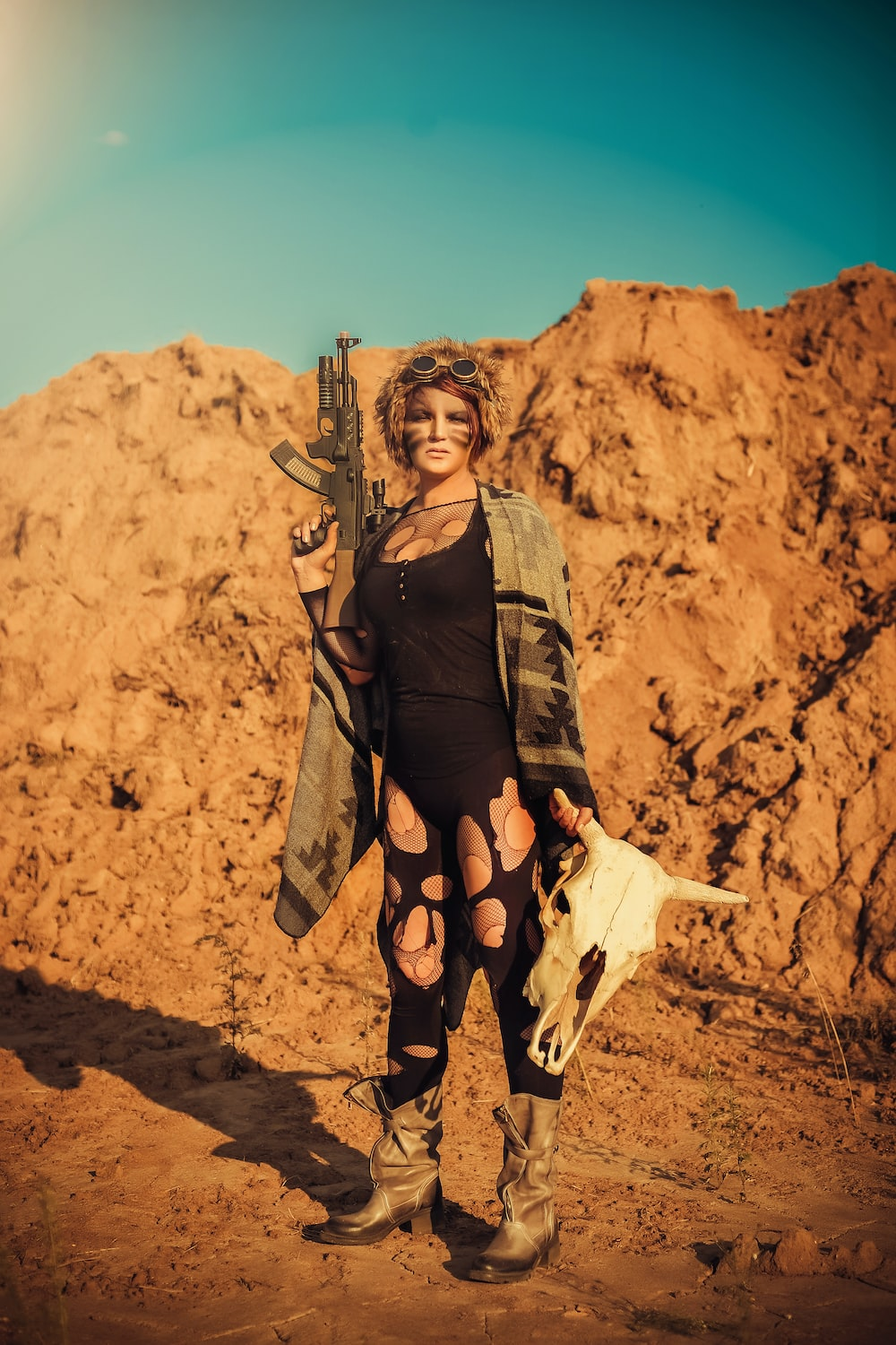 woman holding automatic rifle holding cattle skull at the rocky mountain