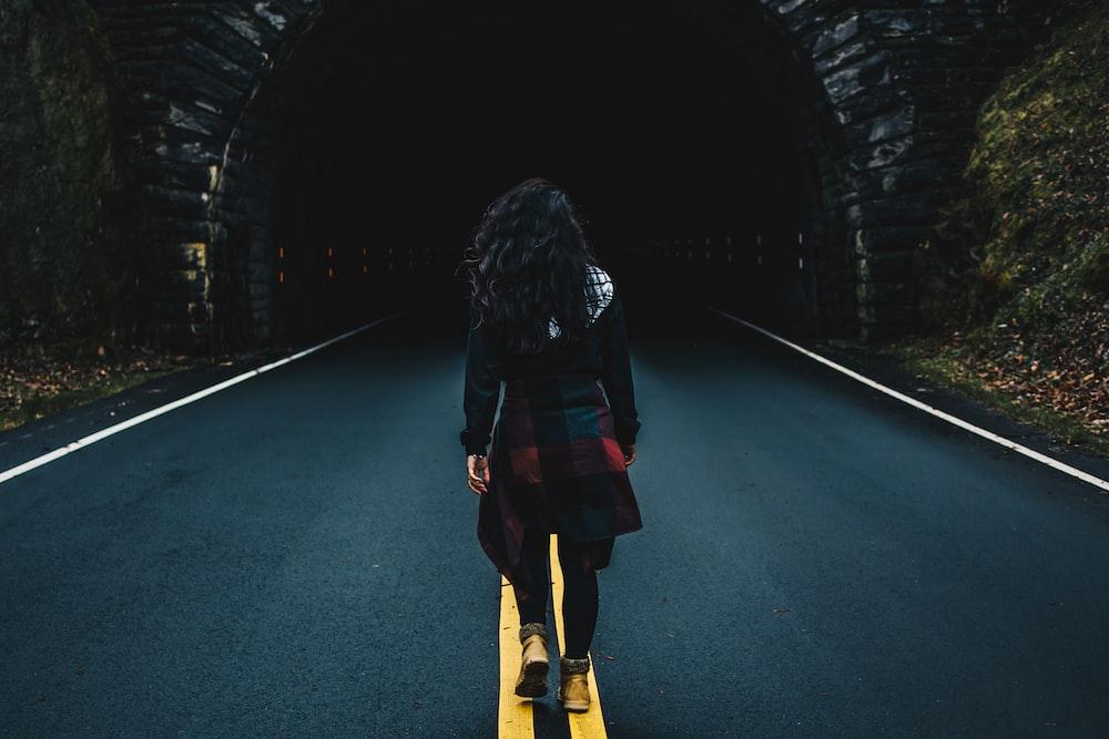 woman wearing black jacket walking on road