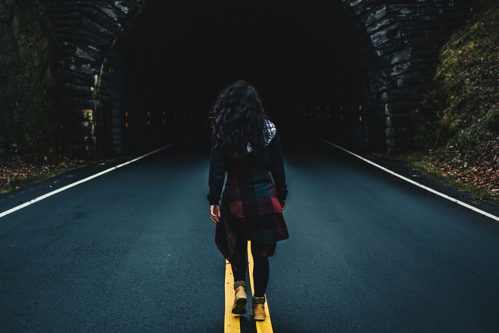 woman wearing black jacket walking on road