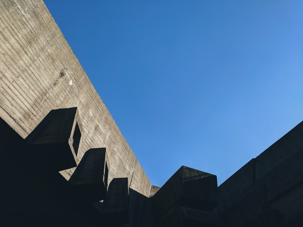 low-angle photography of gray concrete building under calm blue sky
