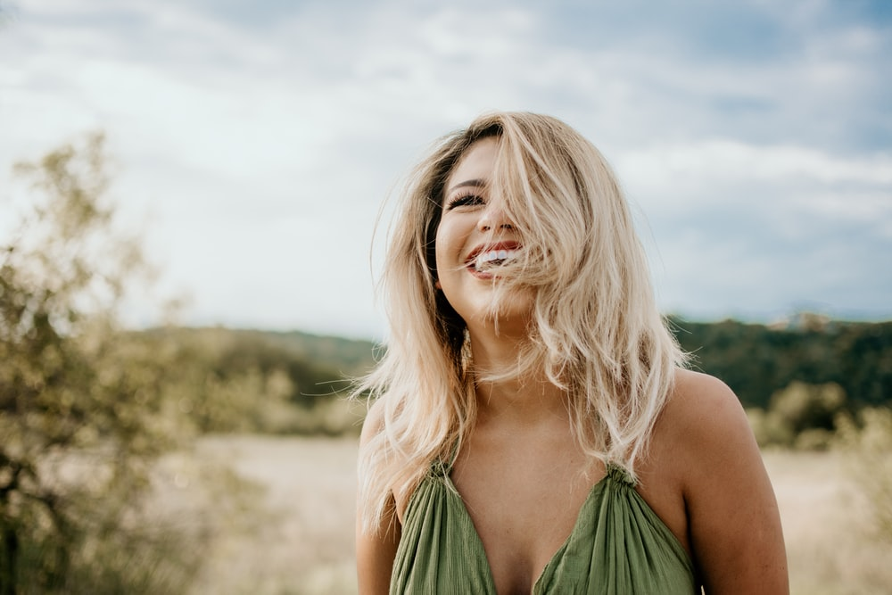 time-lapse photography of laughing woman with hair covering half of her face