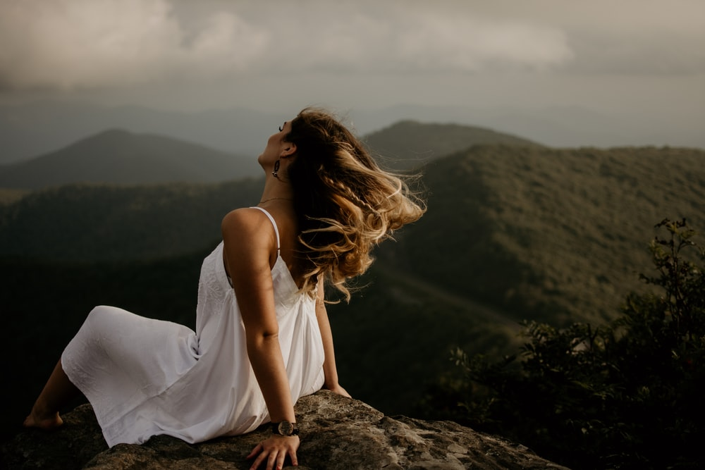 woman in white sleeveless dress sitting on hill