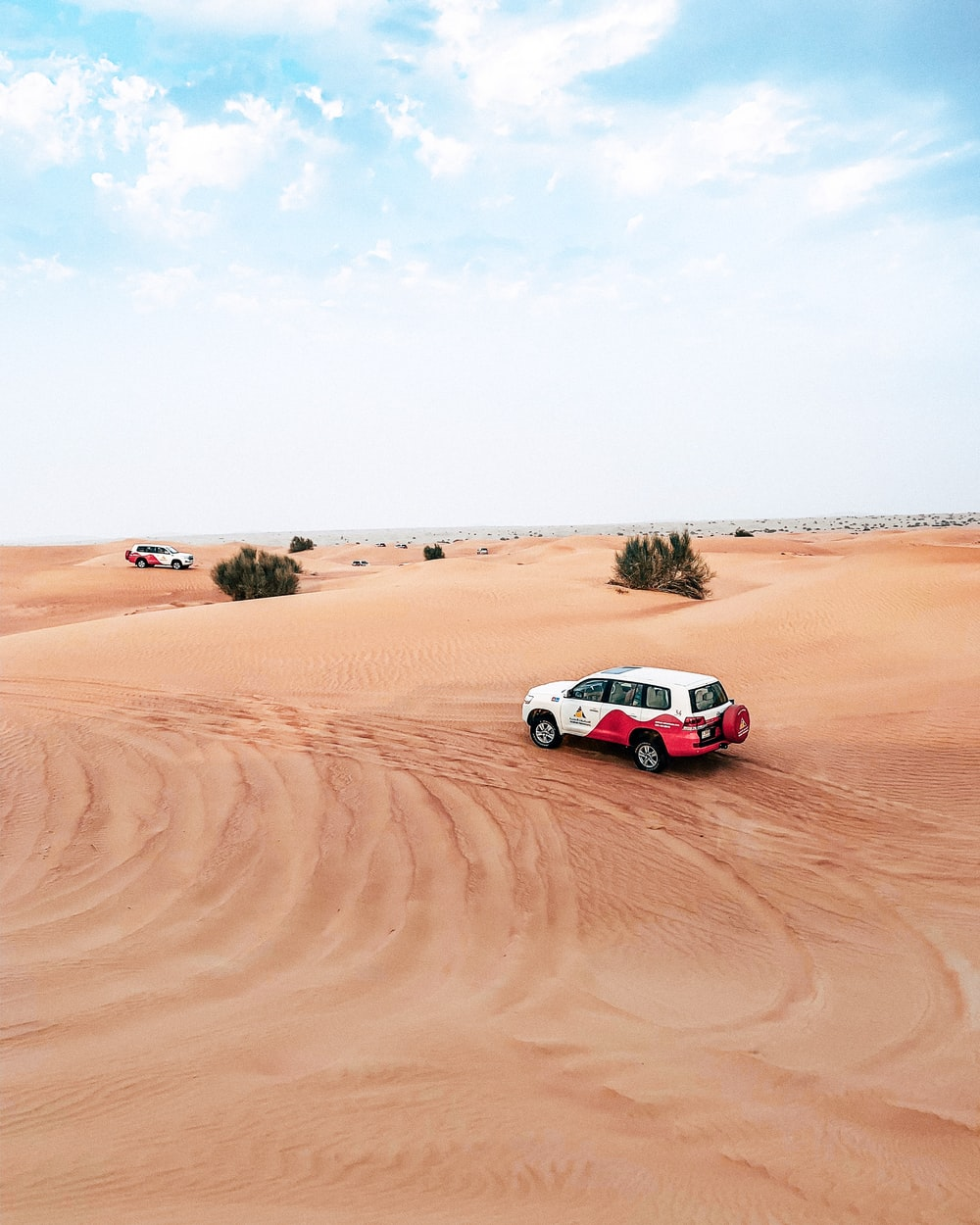 two SUV on sand dunes