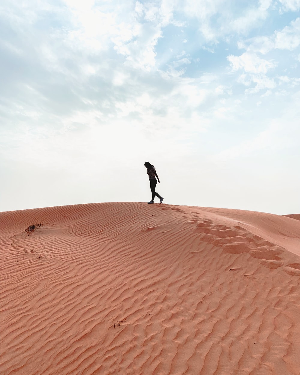 silhouette of woman walking on desert