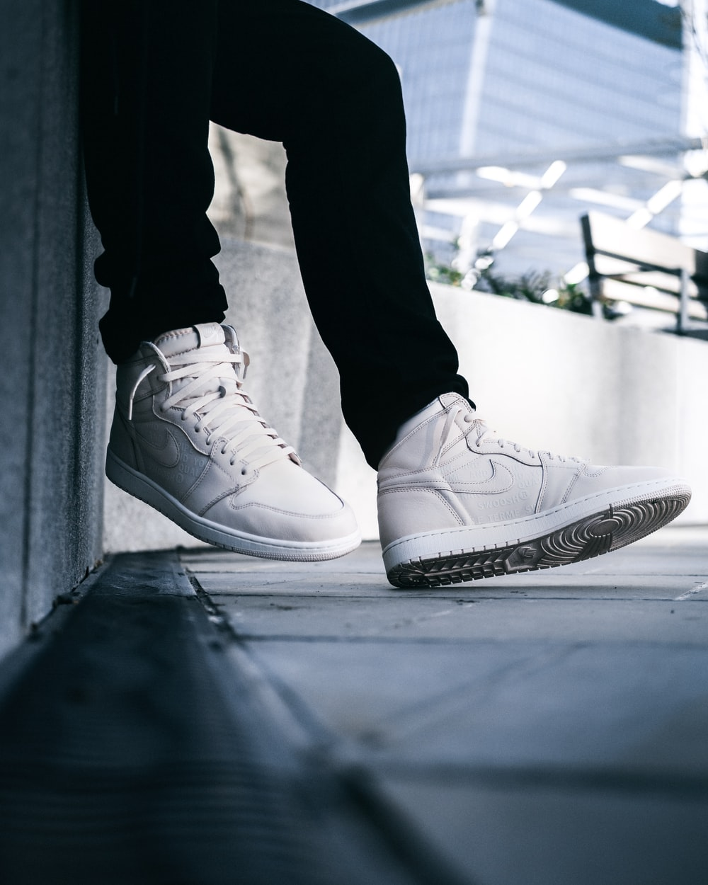 person wearing white Nike mid-rise lace-up sneakers