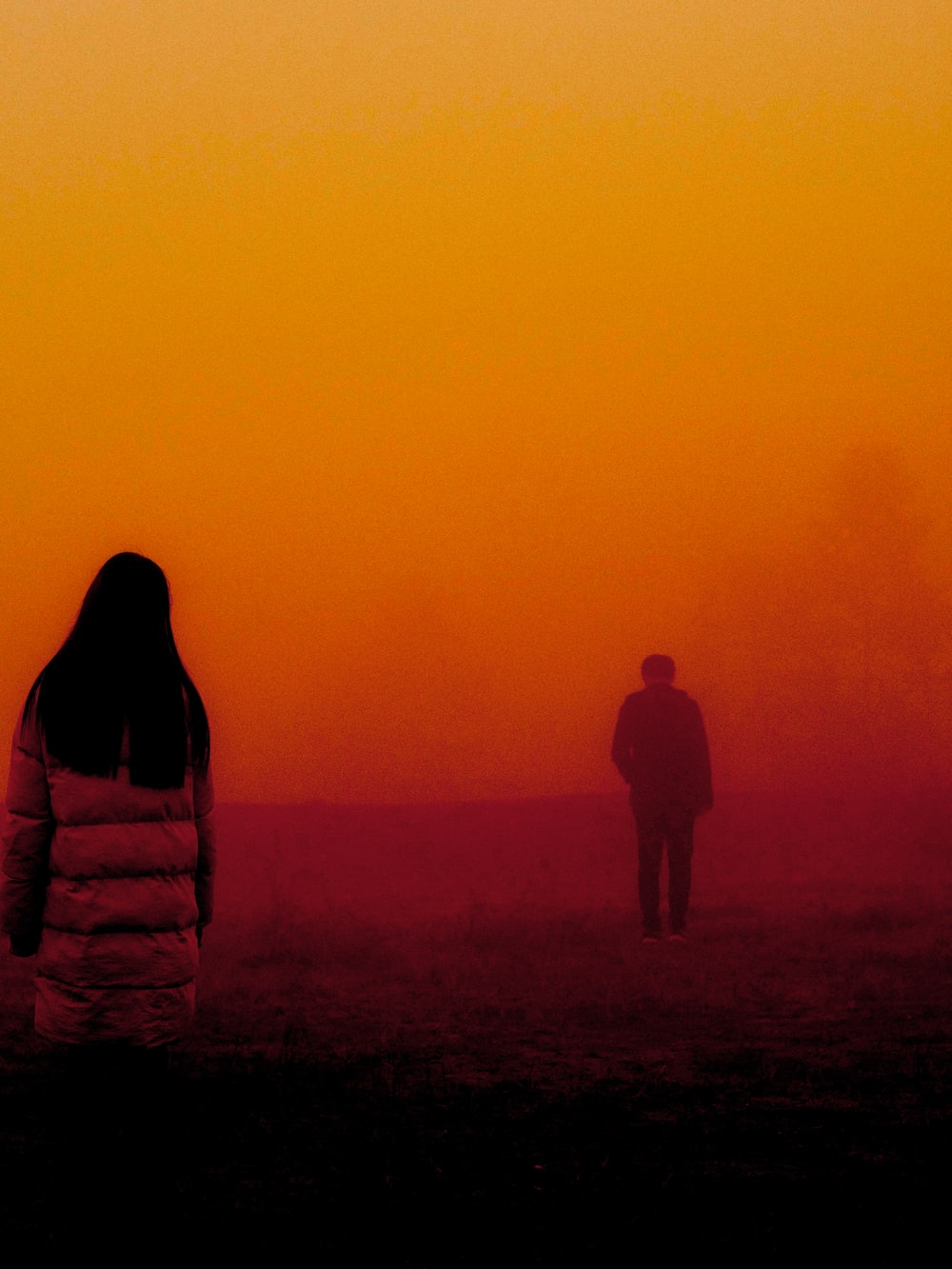 woman wearing coat looking the boy about to walk to away