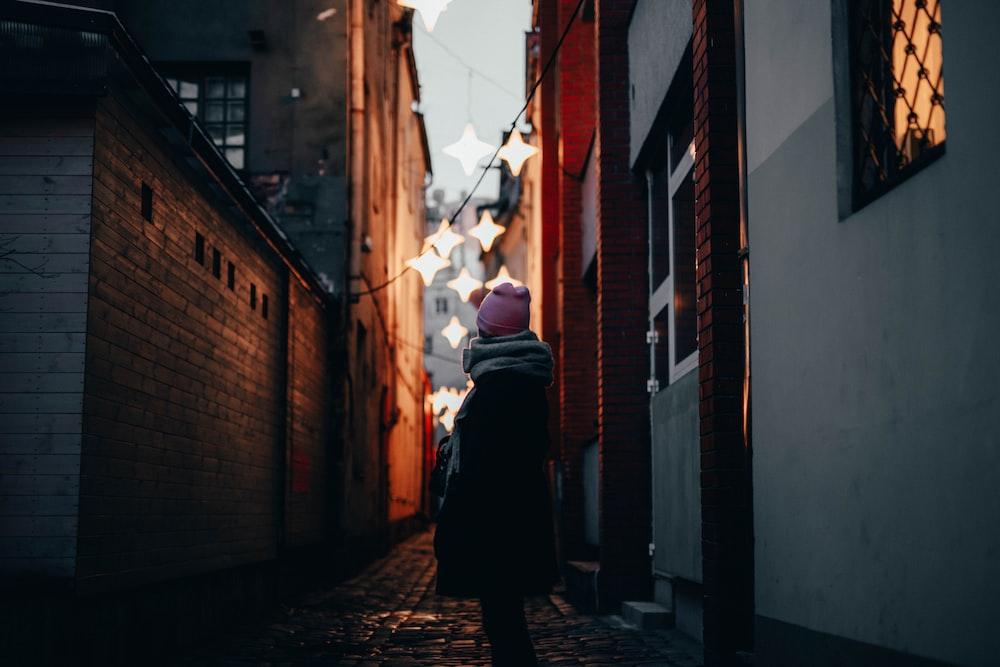 woman standing beside concrete building