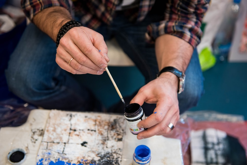 person holding paint bottle and paint brush