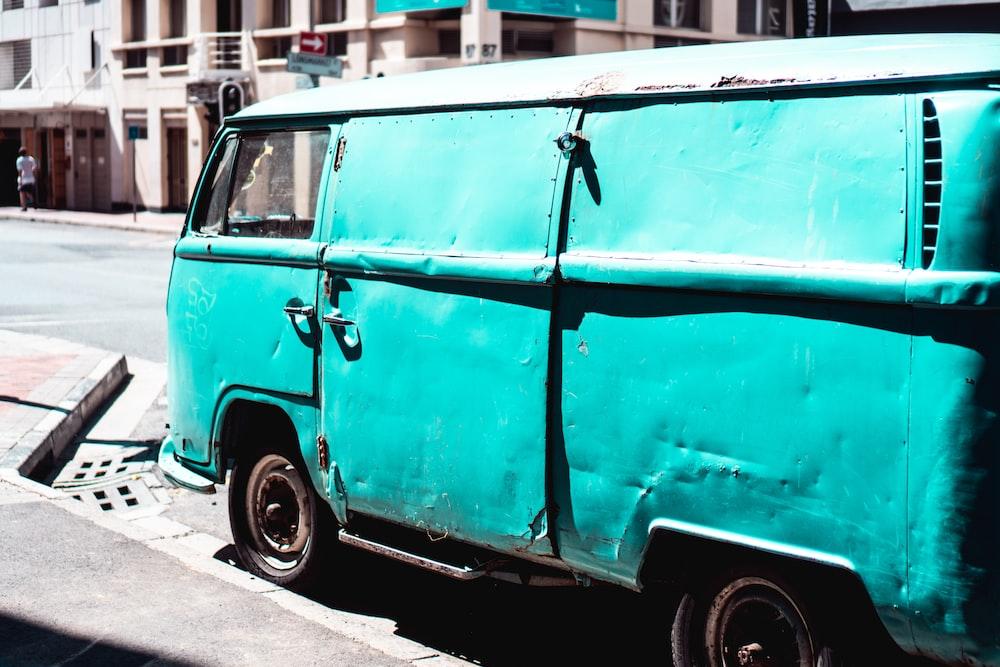 blue van parked beside road
