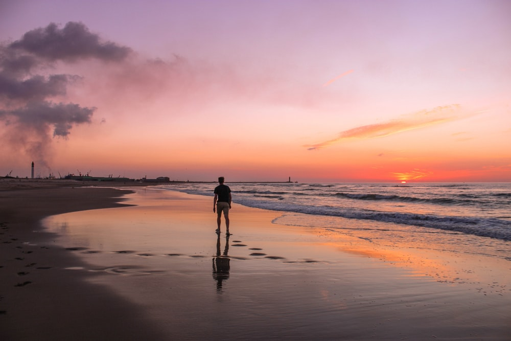 man standing on sea shore during golden hour