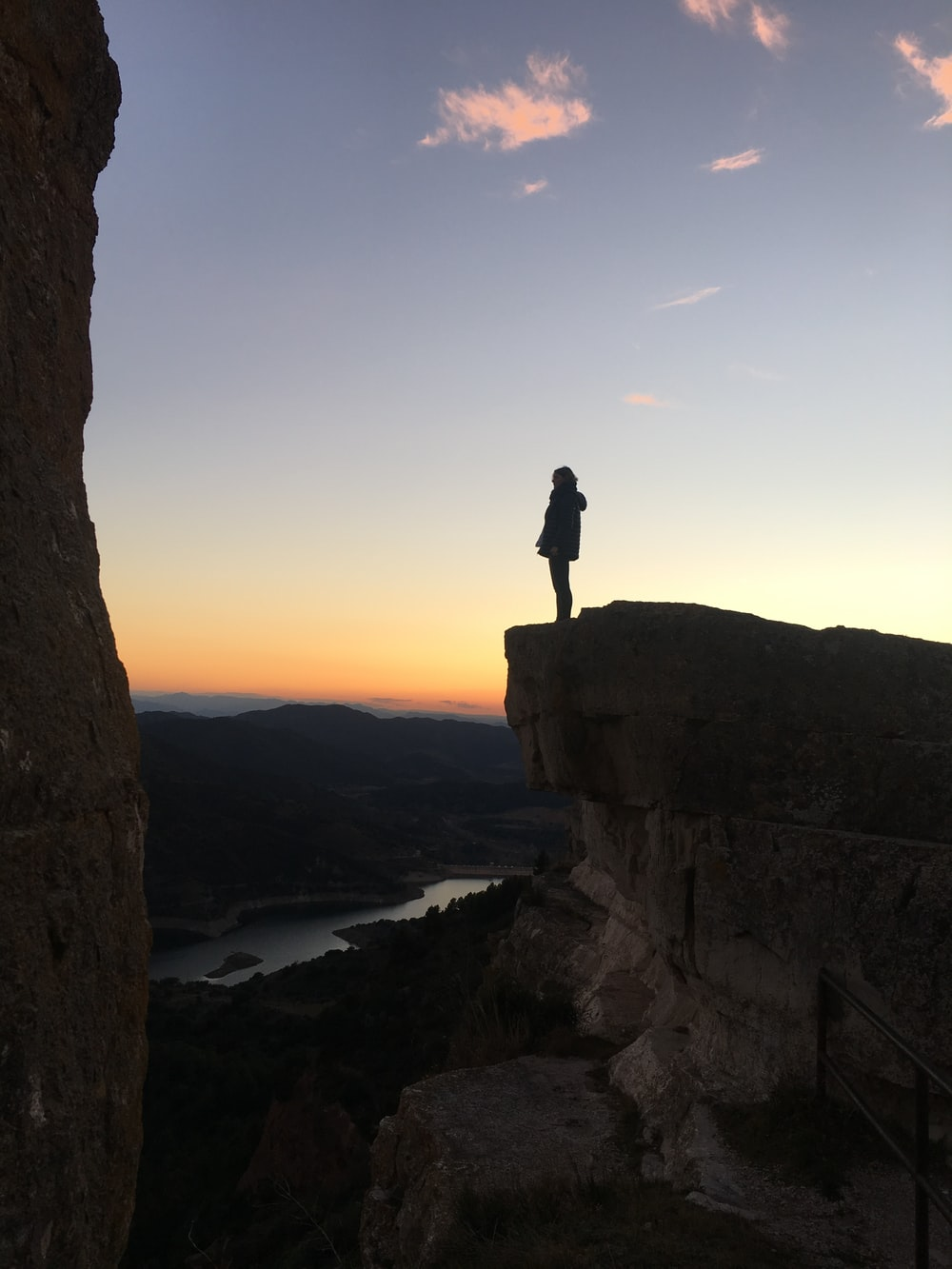 silhouette of woman standing on cliff
