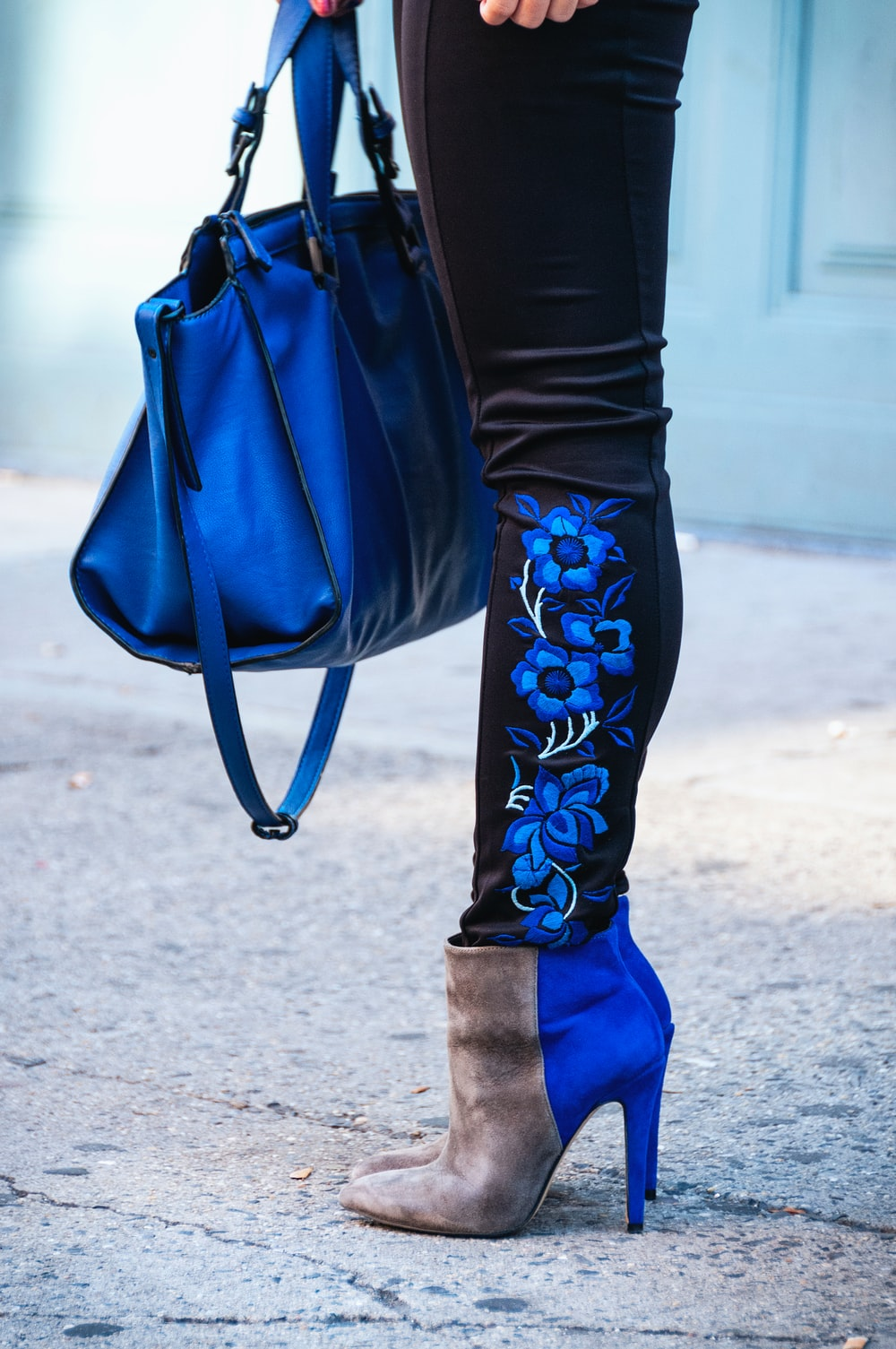 person in black leggings, booties and carrying blue bag