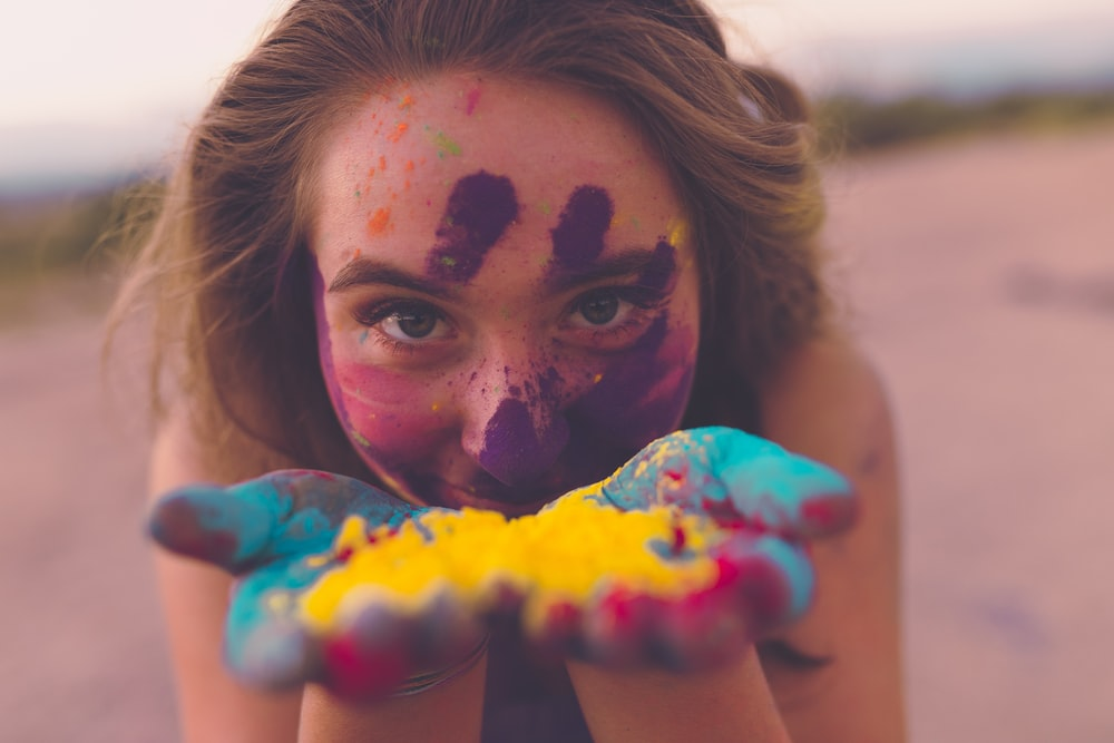 woman with coloring powders on face and hand
