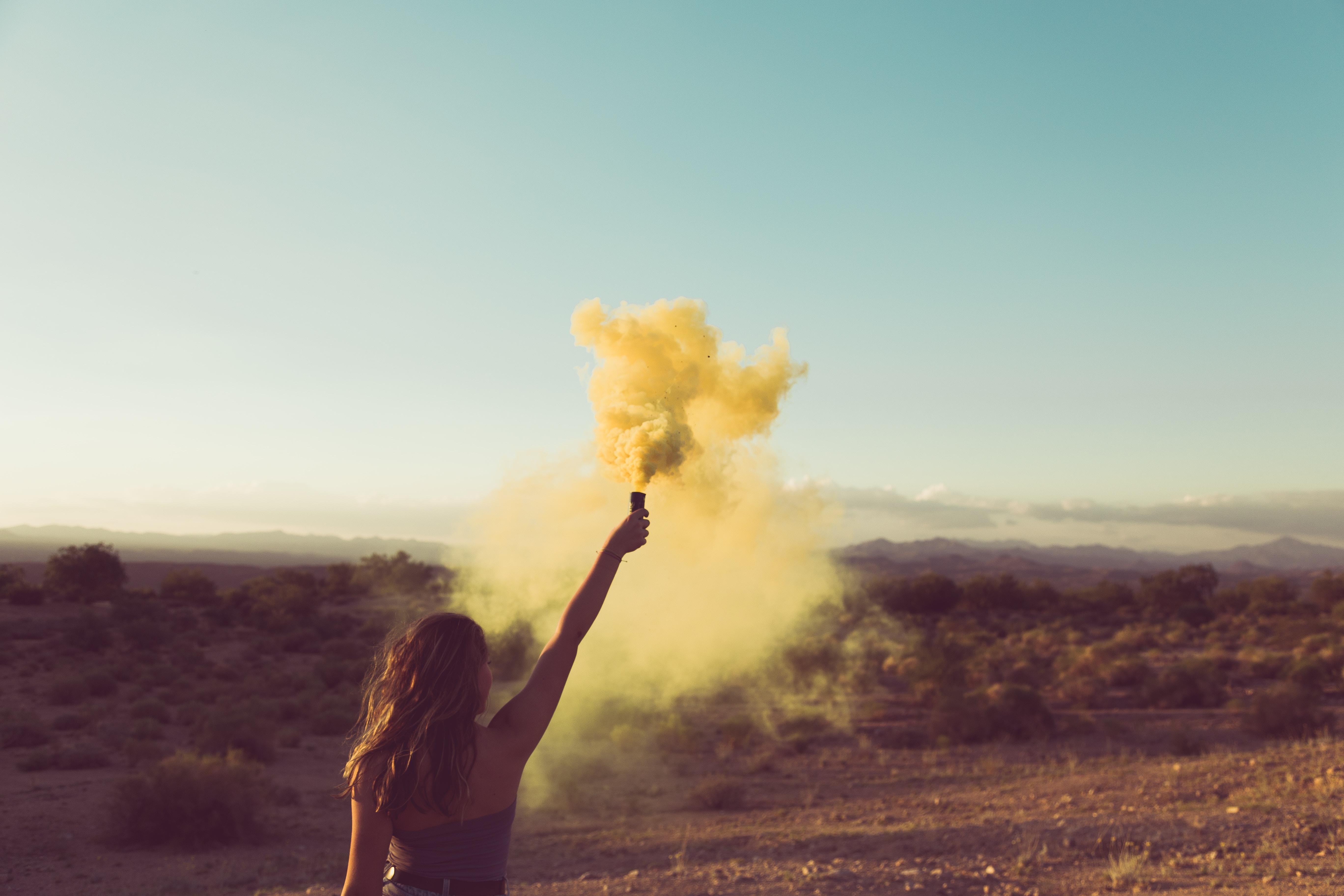 woman standing on desert holding flare