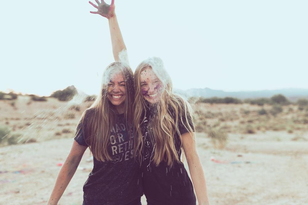 two woman smiling near grass