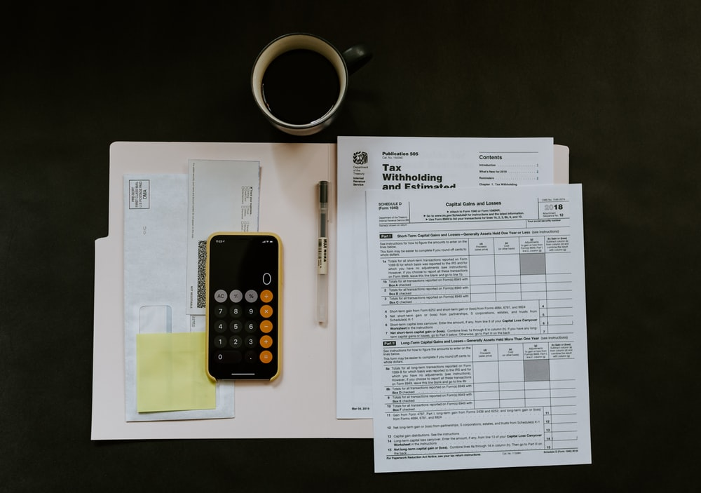 black Android smartphone near ballpoint pen, tax withholding certificate on top of white folder
