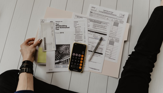 person holding paper near pen and calculator