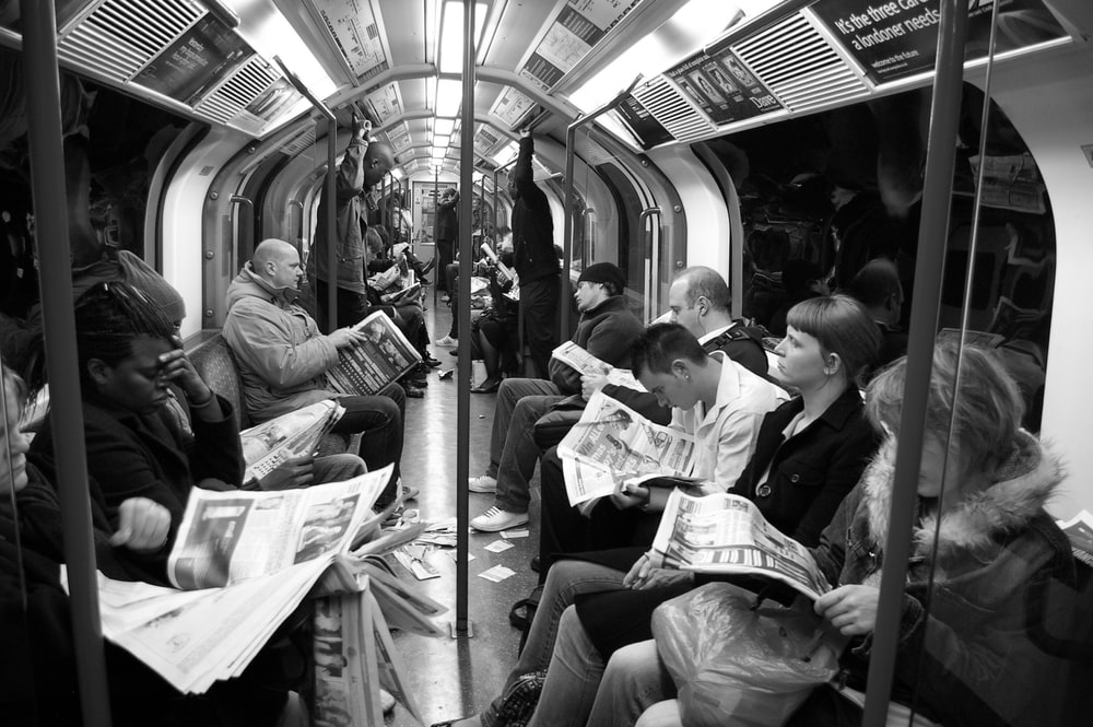 grayscale photo of people sitting on train chairs