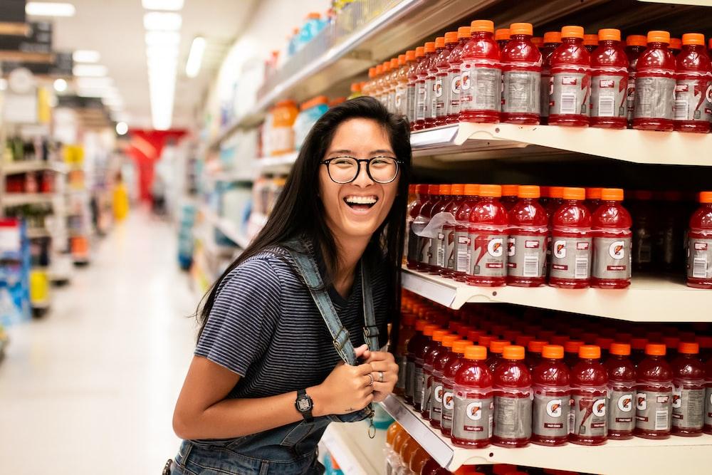 woman laughing while standing beside Gatorade bottlles