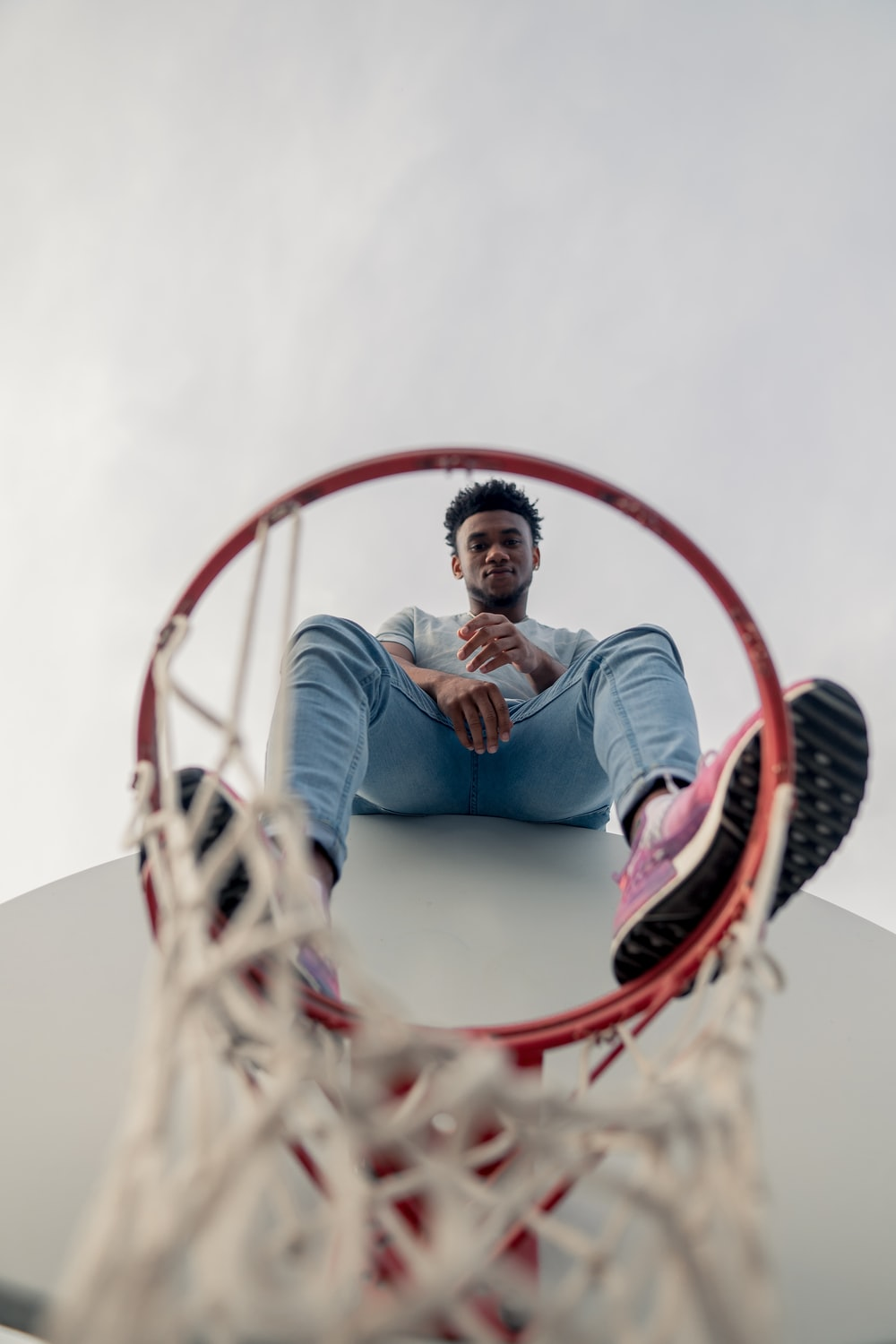 man sitting at the top of basketball hoop