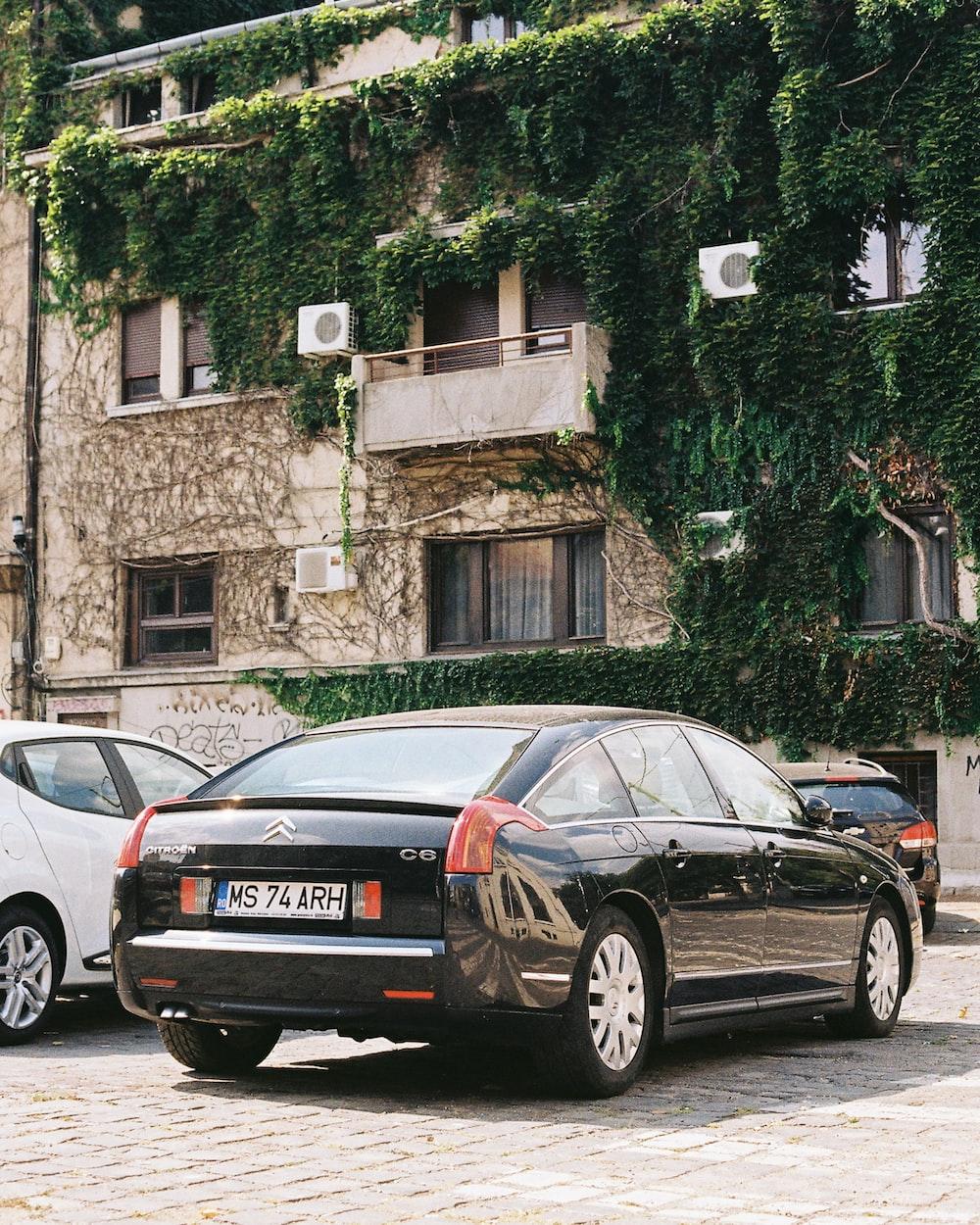 black car parked beside building