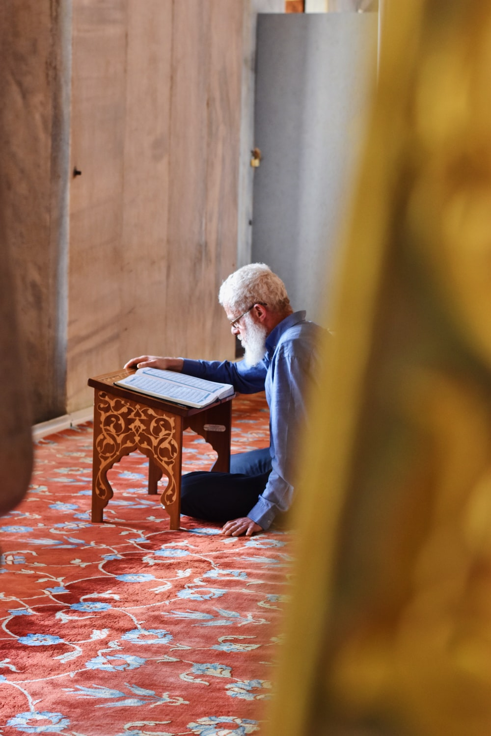 man sitting on area rug reading book on book stand