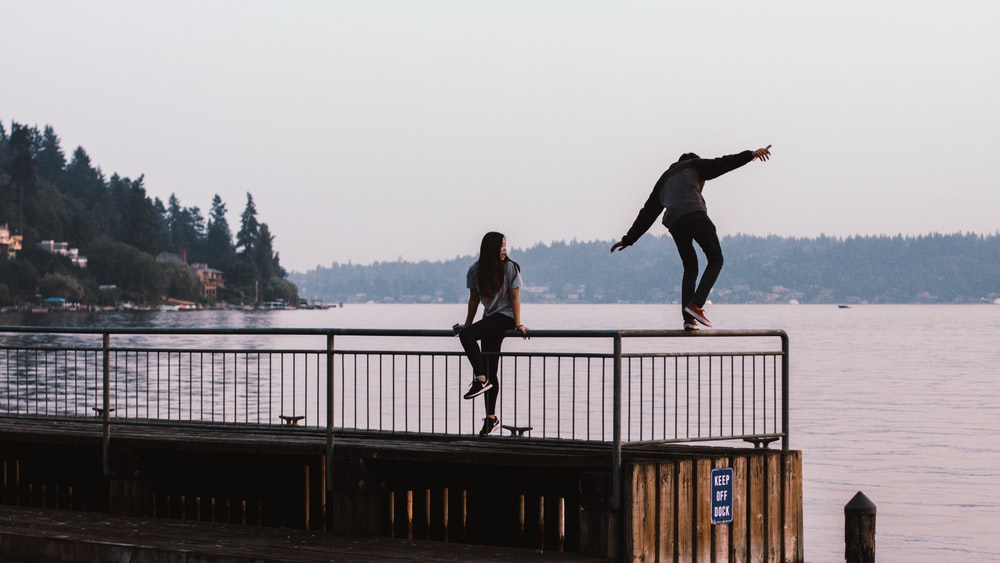 two person standing on handrails during daytime