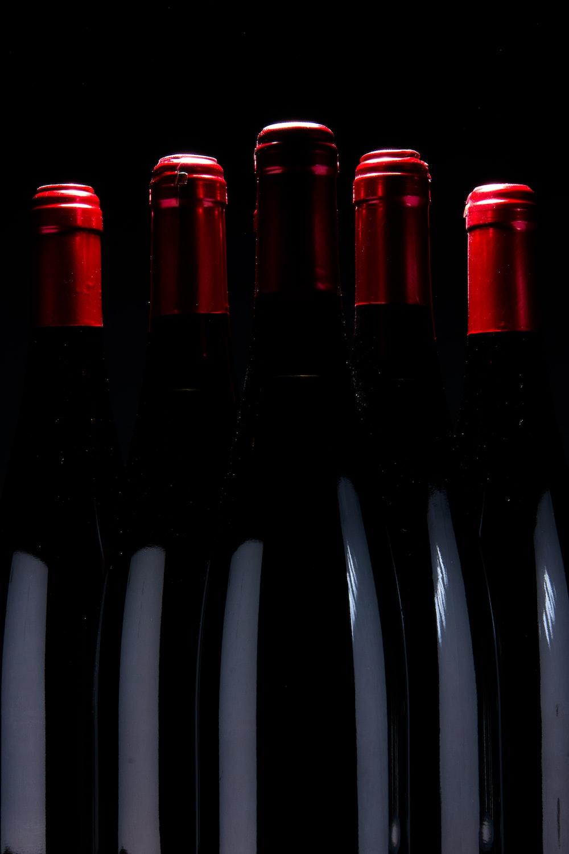 five upright black bottles