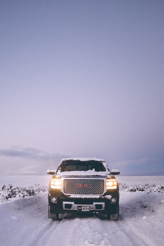black car travelling on snow