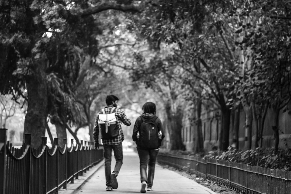 grayscale photography of couple on road