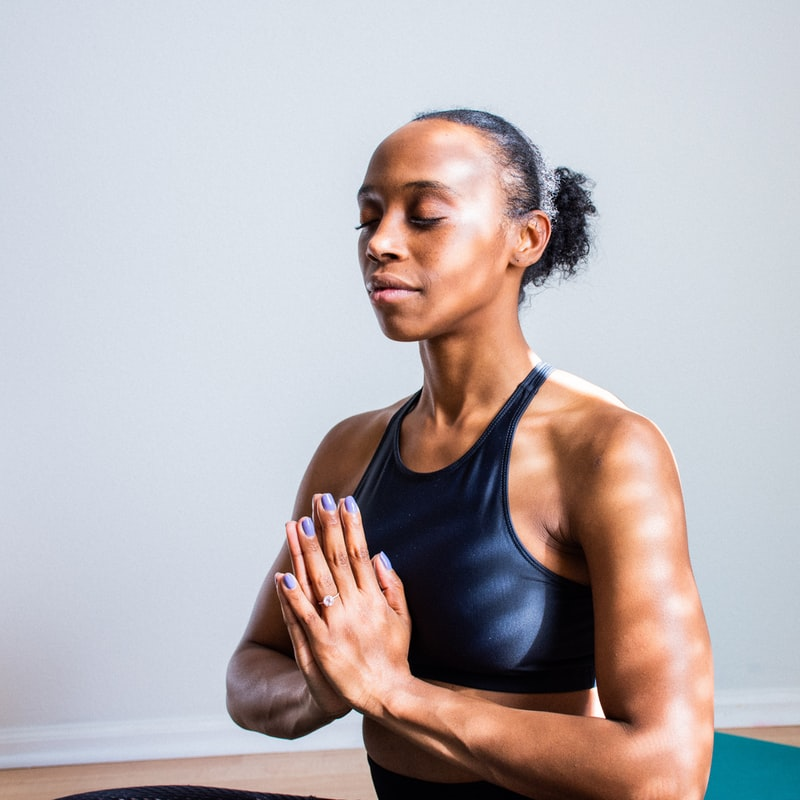 A black woman seated and meditating. Her hands are in prayer position, her eyes closed.