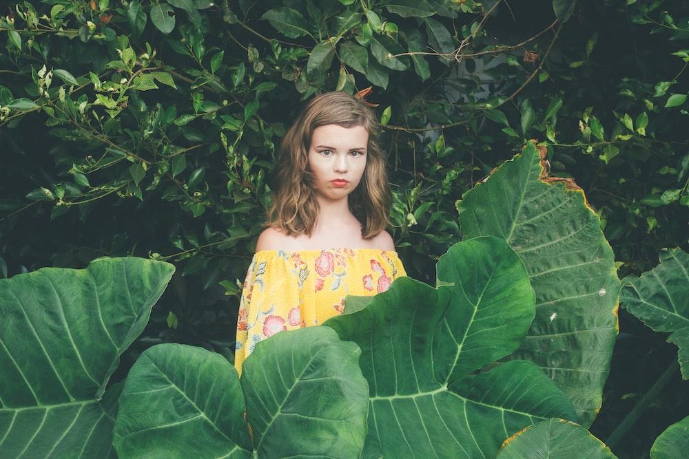 woman standing behind leaf plant