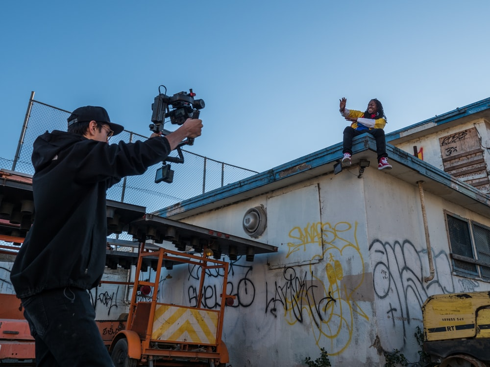man taking a video of a person on roof
