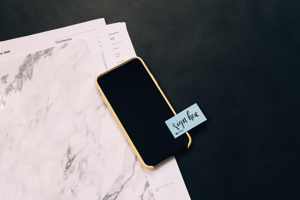 black smartphone on white pad