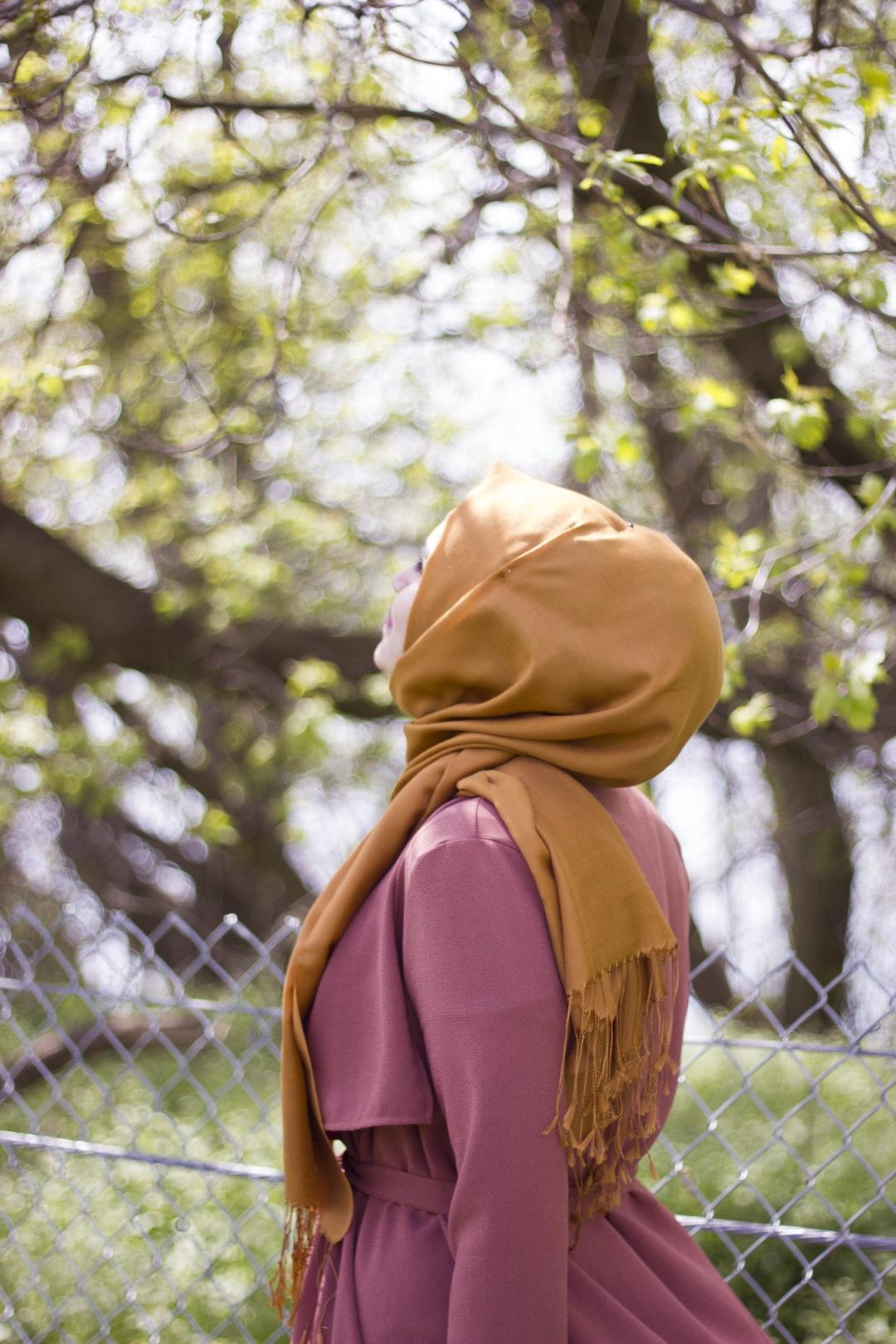 Woman in hijab enjoying the summer breeze under trees.