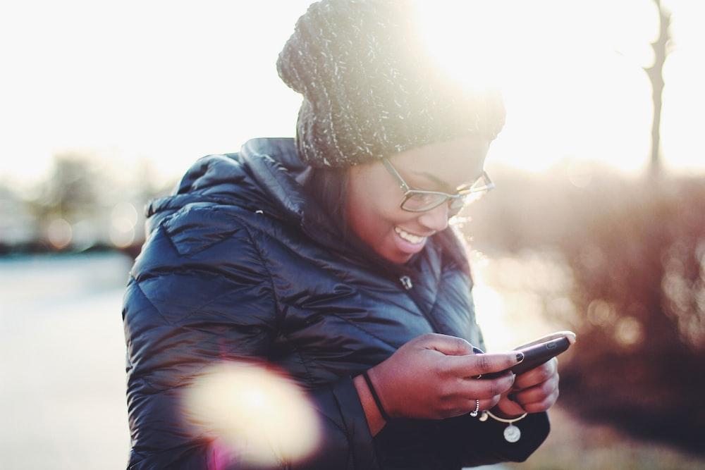 スマートフォンを使用して黒いコートを着ている笑顔の女性