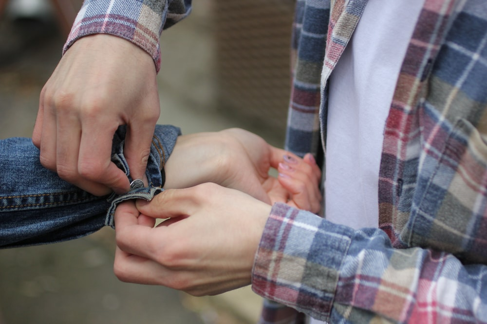 person fixing man's jacket