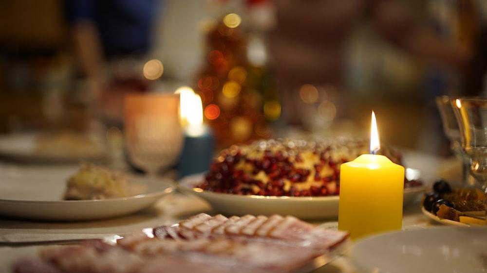 lighted pillar candles beside plates