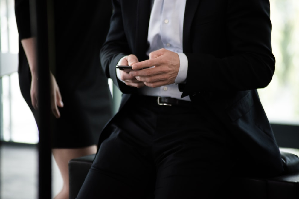 man in black suit with phone in hand