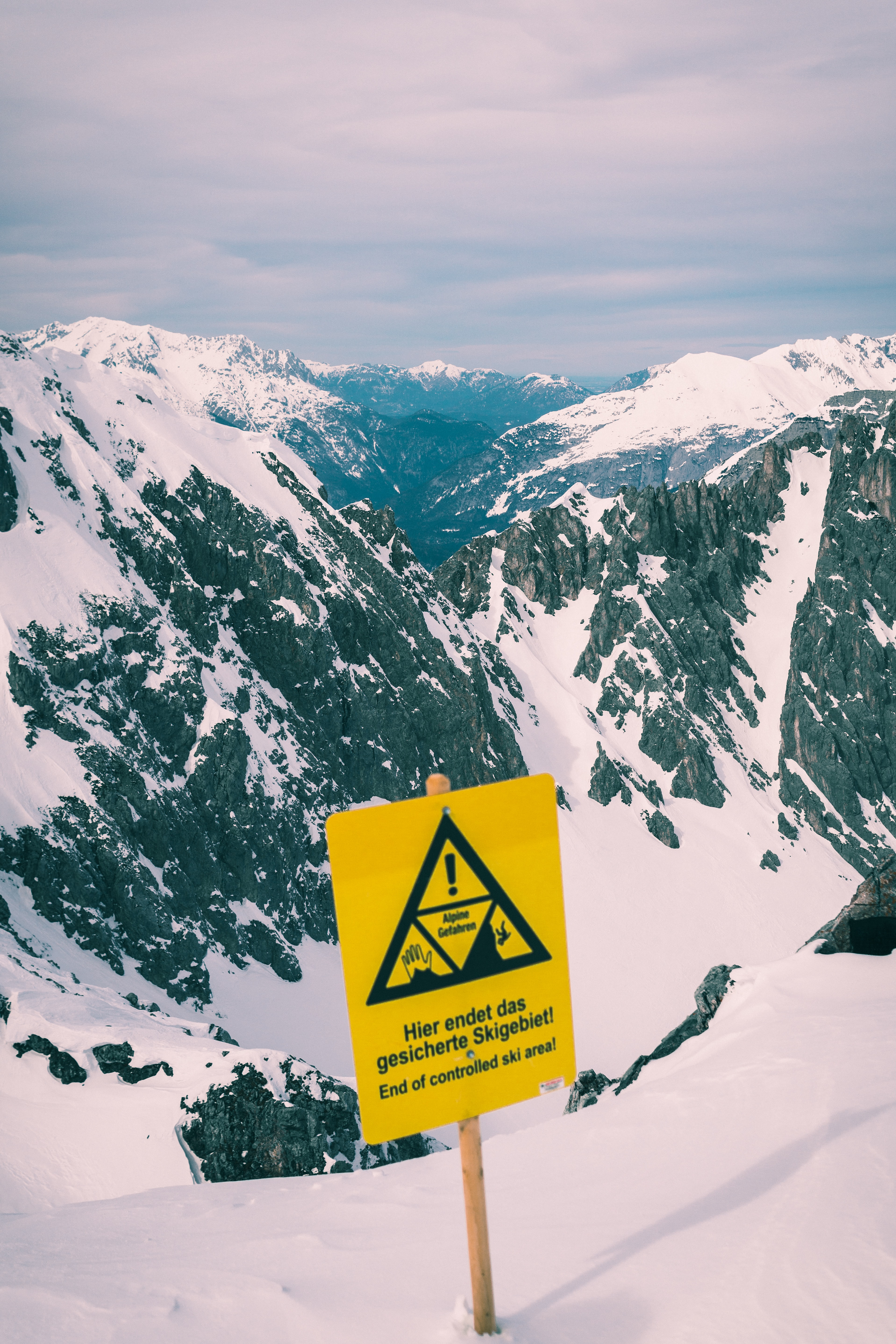 yellow and black sign on snow capped mountain