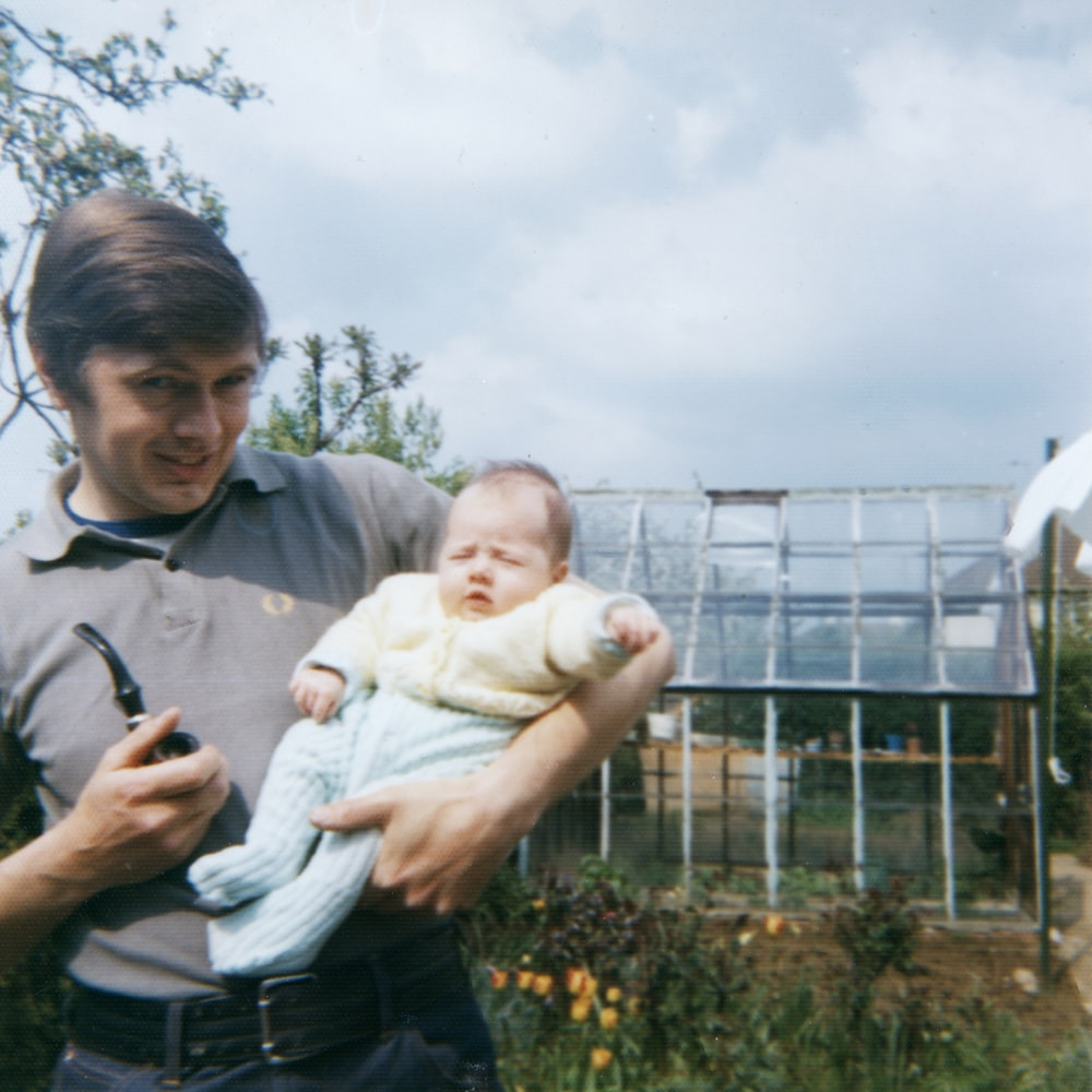 man in grey polo shirt holding baby