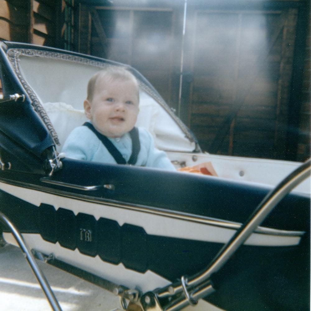 baby sitting on black stroller smiling