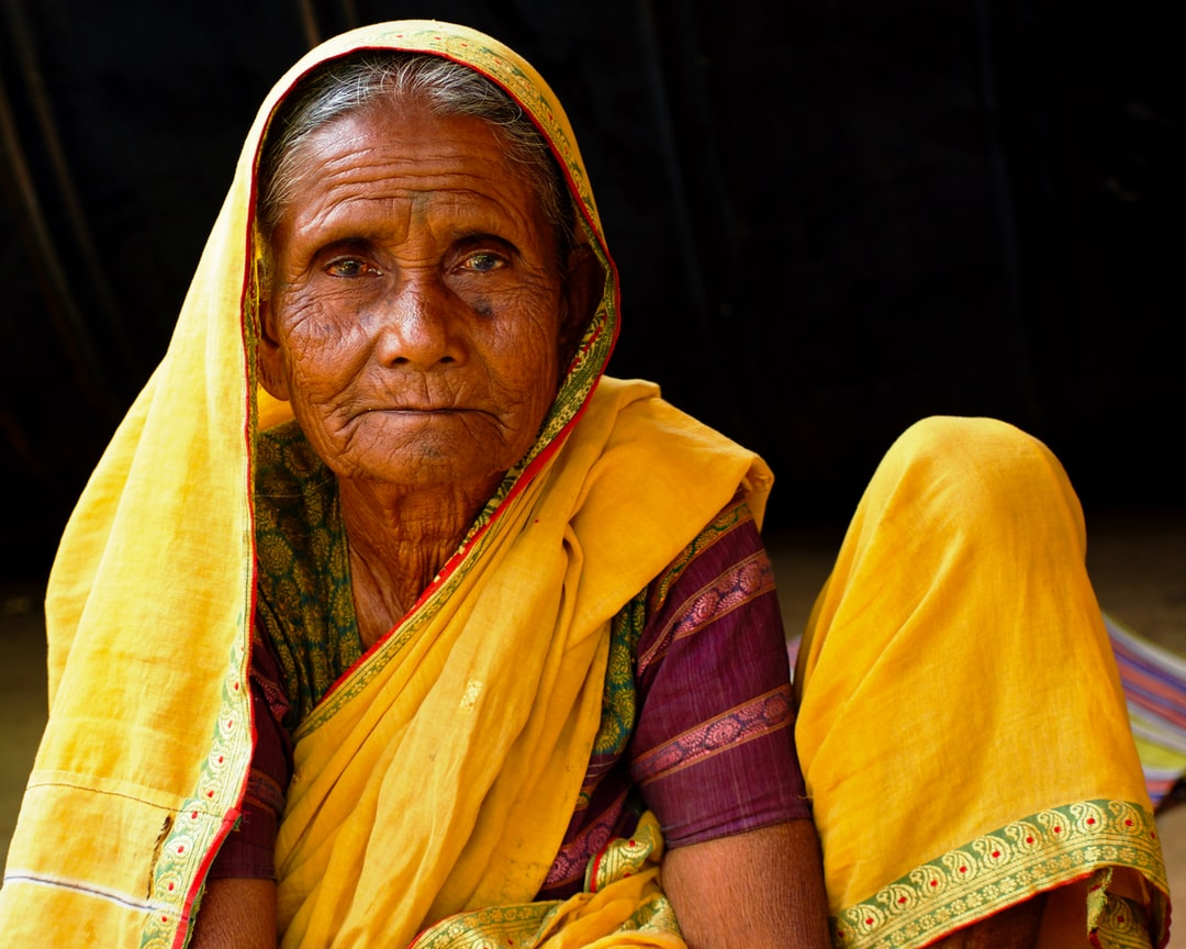 An old Indian village woman dressed in a vibrant traditional saree (Indian attire)