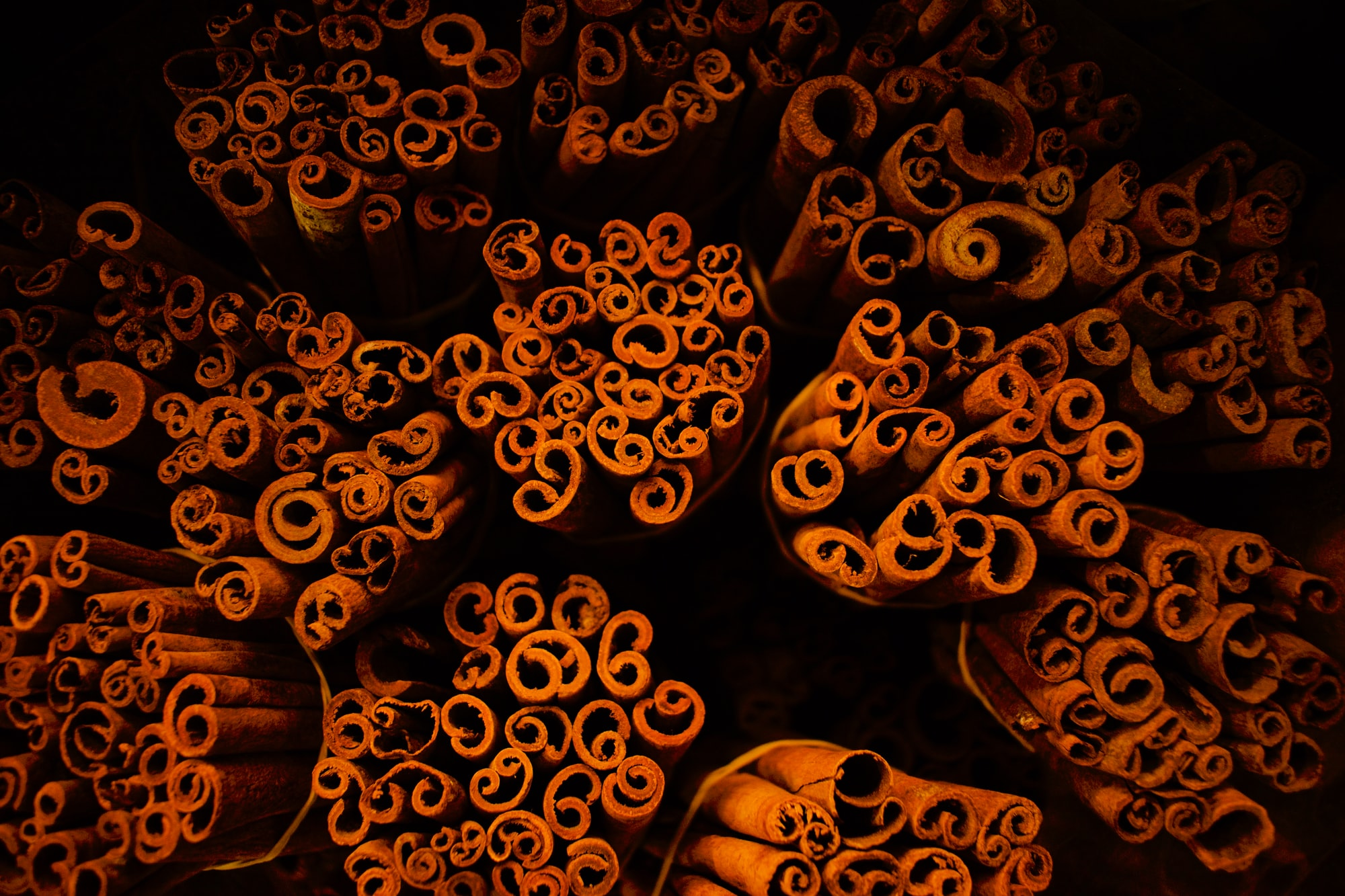 A picture taken at a spice stall in the famous spice market in Dubai showing an interesting pattern created by cinnamon sticks on display. With a limited light fallling on the subject, the background automatically became dark creating a deep effect.