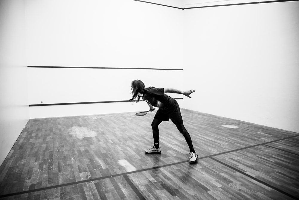 grayscale photography of person holding racket