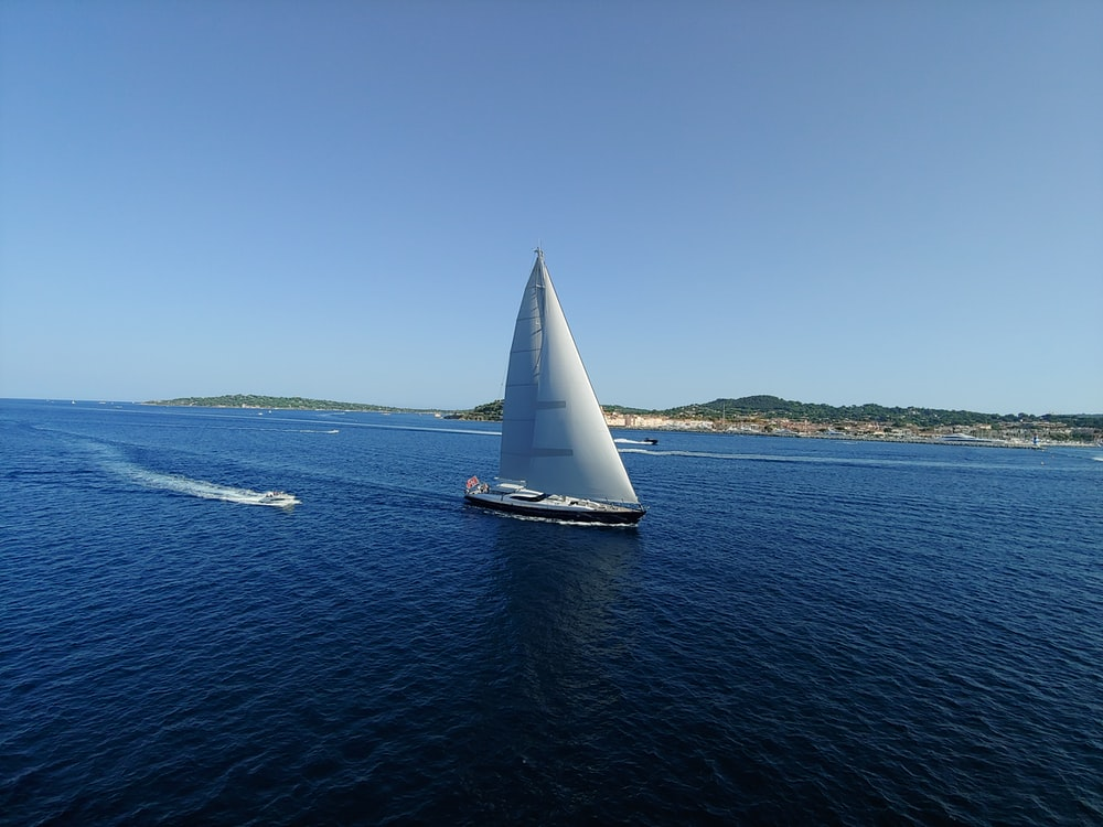 black sail boat on sea