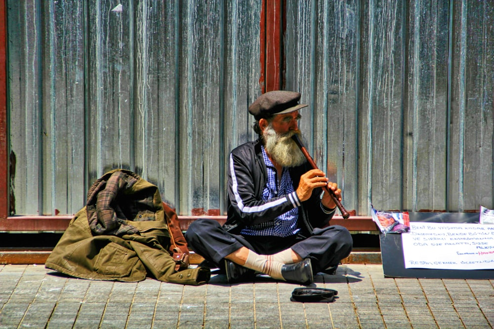 man playing flute sitting on the side of the street
