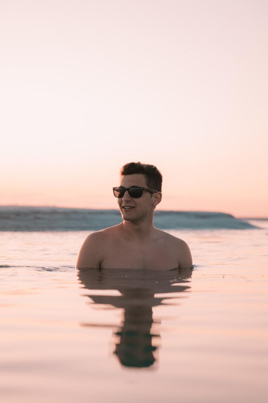 man in sunglasses dipping in ocean